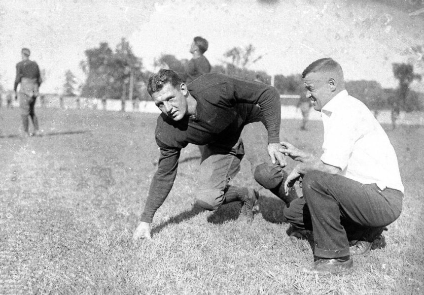 "FILE--Red Grange, half-back for the University of Illinois, poses with coach Bob Zuppke, right, during football practice, in this 1925 file photo. Grange is a featured played in ESPN's ""Rites of Autumn,"" a 10-part series about college football that debuts on the cable channel Friday, Oct. 12, 2001. (AP Photo) ORG XMIT: NY353"